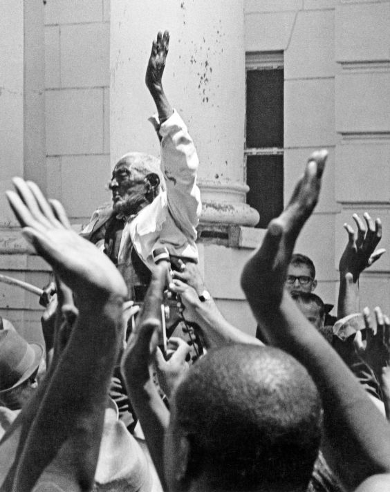 106-year-old El Fondren is hoisted victoriously above crowd after registering to vote, Batesville, Mississippi, June 11, 1966.