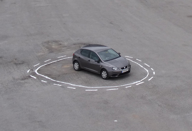An artwork by James Bridle that shows a car surrounde by a solid white line an a broken white line.
