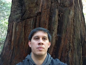 Andrew Berger standing before a California redwood tree
