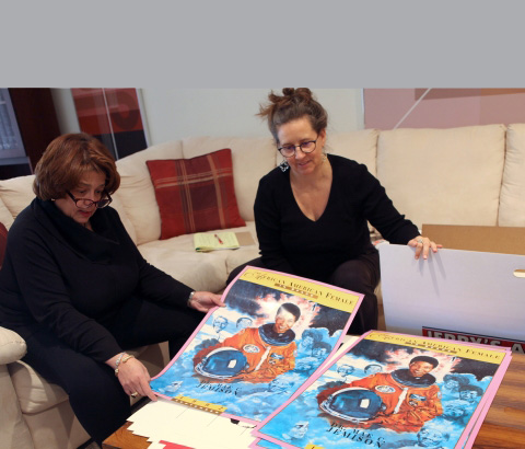 Cheryl D. Miller (left) showing Regina Roberts (right) the poster design her firm created to commemorate Mae Jemison, the first African American Woman to go up in space, orbit on the Space Shuttle Endeavour. -- Lisa Barlow