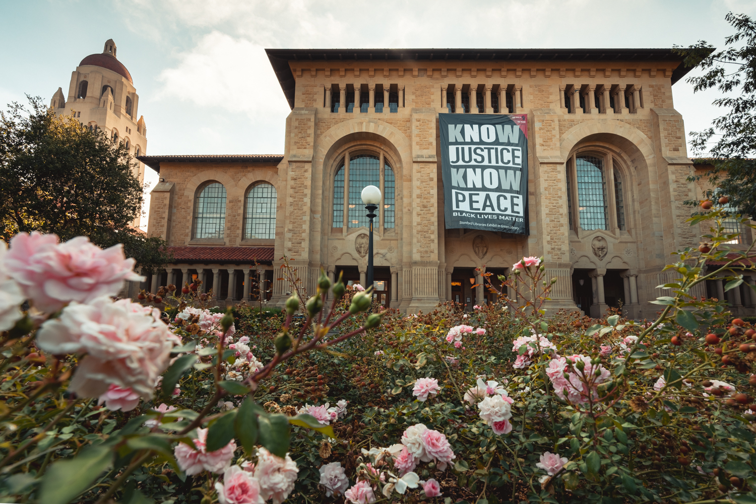 """A large banner featuring the words """"Know Justice Know Peace"""" (a play on a popular protest chant) was unfurled Friday across the front of Green Library during an online livestream event. (Image credit: Andrew Brodhead)"""