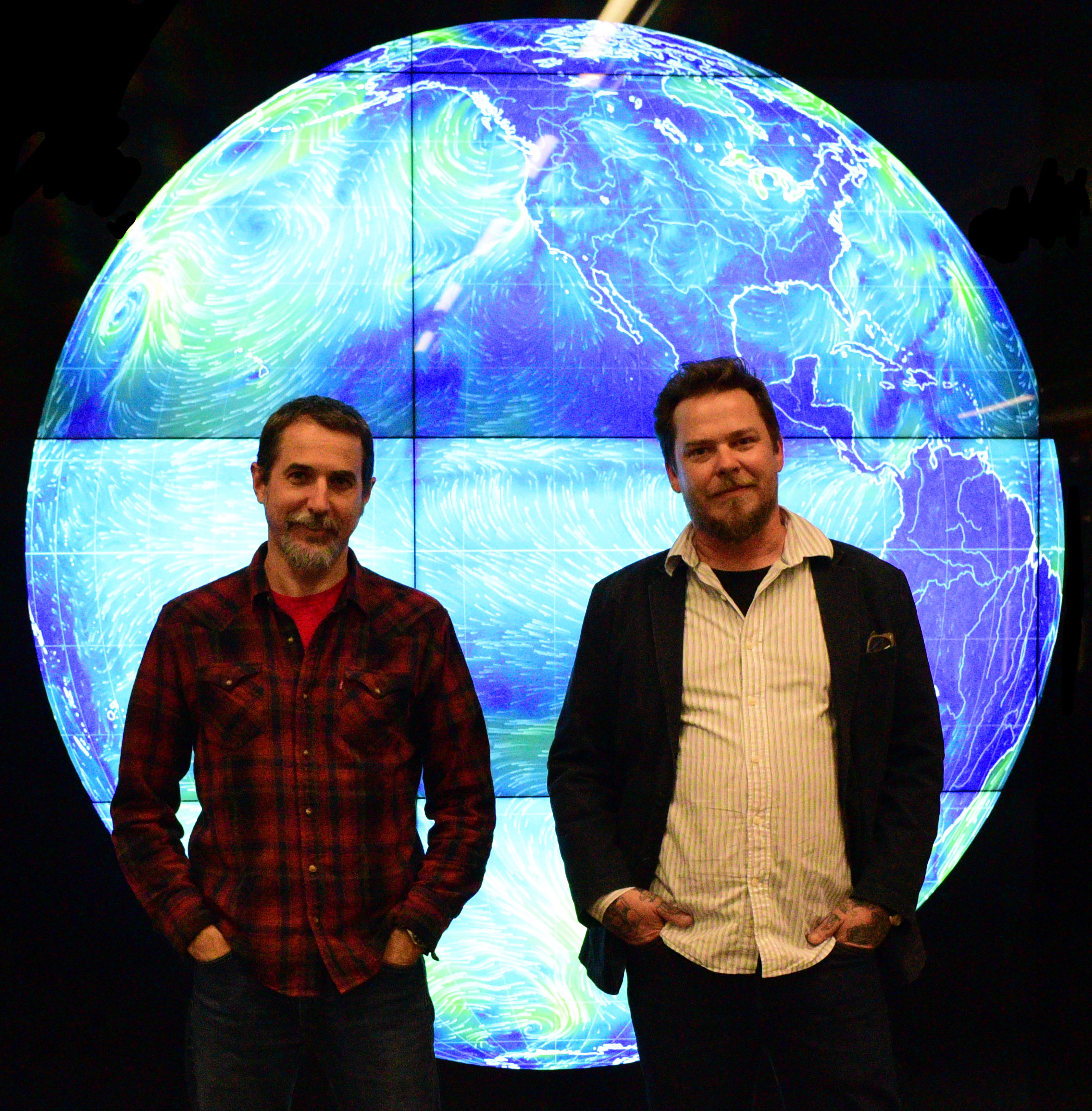 Geospatial instruction and reference specialist David Medeiros, left, and Geospatial manager Stace Maples stand in front of one of the Rumsey Center's large screens used for displaying maps. Photo credit: Danielle T. Tucker