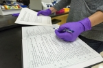 A scientist in the Dekas lab enters information into a lab notebook.