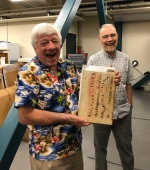 Peter Whidden and John Mustain holding a rare book bound in medieval manuscript