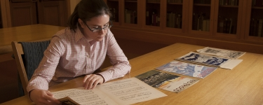Humanities Center Fellow Amanda Cannata examines some of the World's Fair music that is part of the William R. and Louise Fielder Sheet Music Collection at Green Library.