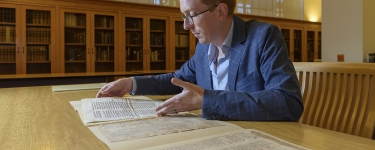 Rowan W. Dorin, assistant professor of history, with the miscataloged parchments whose mystery he is working to solve. (Image credit: L.A. Cicero)