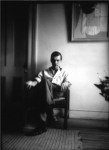 Moody black and white photo of Weldon Kees sitting in chair