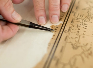 Debra Fox, a paper conservator in the Conservation Lab, aligns fragments of an 1853 map of the North Pacific Ocean to ensure that the map is as complete as possible before she lines it with Japanese paper. Courtesy: Linda A. Cicero, Stanford News Service