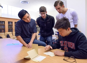 Junior Alexander Wang, T.A., grad student Peter Hick, senior Teun de Planque, and freshman Berber Jin examine a pamphlet on Martin Luther King, Jr. written by Mao Zedong.