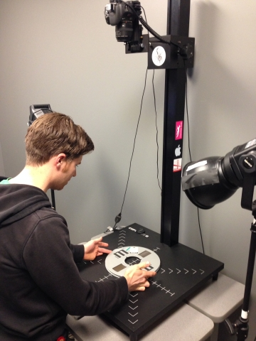 Production Coordinator Geoff Willard photographs an audio reel to be digitized at SMPL