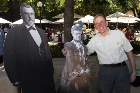 Zachary Baker with life-size cutouts of Jane and Leland Stanford.