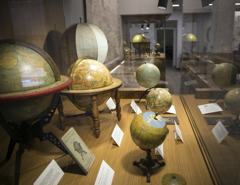 a glass cabinet filled with antique globes