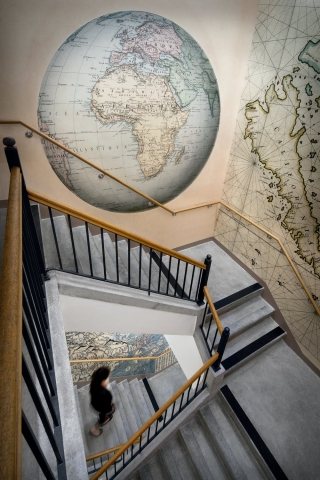 Stairwell to the Rumsey Center. Walls are covered in murals of maps.