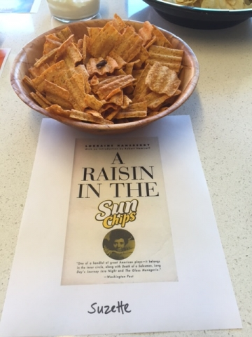 A bowl of Sun chips with a raisin on top of a chip