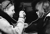 Two women sharing head phones, photo by Sigfrid Lundberg