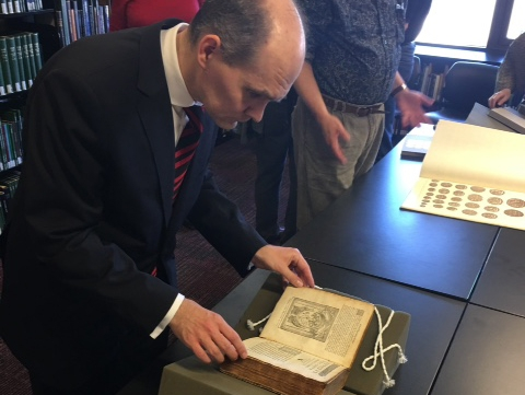 Dr. Woytek examining a 1567 edition of works by Guillaume Du Choul