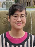 Photo of Angela Tsai standing in front of Green Library fountain.