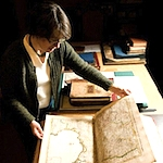Julie Sweetkind-Singer, head librarian of the Branner Earth Sciences Library, looks through a world atlas published in France in 1742, the Atlas Nouveau by de Lisle, part of the David Rumsey Map Collection.