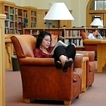 A student enjoys one of the comfortable chairs in the Lane Reading Room